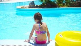 Kleines Mädchen mit aufblasbarem Gummikreis im Swimmingpool stock footage