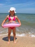 Kleines Mädchen mit aufblasbarem Kreis in dem Meer Lizenzfreie Stockbilder