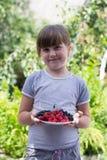 Kleines Mädchen mit Beeren in den Händen lizenzfreie stockbilder
