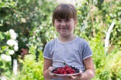 Kleines Mädchen mit Beeren in den Händen stockfotos