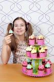 Kleines Mädchen mit beschmieren Gesicht und Muffins backt zusammen Stockbild