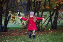 Kleines Mädchen mit Blättern im Herbstpark Stockfotografie