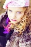 Kleines Mädchen mit blauen Augen im rosa Hut, der im Wald sitzt Lizenzfreies Stockbild