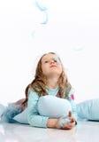 Kleines Mädchen mit blauen Kissen und Federn Stockfotos