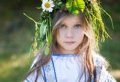 Kleines Mädchen mit Blumenkranz Stockbilder