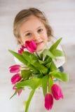 Kleines Mädchen mit Blumenstrauß von Tulpen Stockbilder