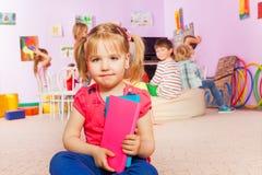 Kleines Mädchen mit Buch in der Klasse Stockfotografie