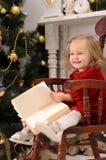 Kleines Mädchen mit Buch im Weihnachtsinnenraum lizenzfreies stockbild