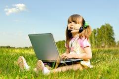 Kleines Mädchen mit Computer Stockfotografie