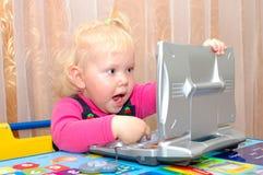 Kleines Mädchen mit Computer des Kindes (Notizbuch). Lizenzfreie Stockbilder