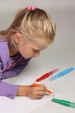 Kleines Mädchen mit dem blonden Haar zeichnet Stockfoto