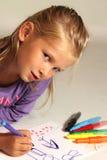 Kleines Mädchen mit dem blonden Haar zeichnet Stockbilder
