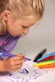 Kleines Mädchen mit dem blonden Haar zeichnet Lizenzfreie Stockfotos
