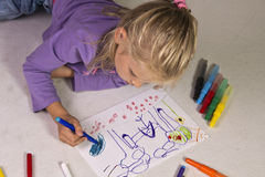 Kleines Mädchen mit dem blonden Haar zeichnet Lizenzfreie Stockfotografie