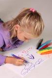 Kleines Mädchen mit dem blonden Haar zeichnet Lizenzfreies Stockbild