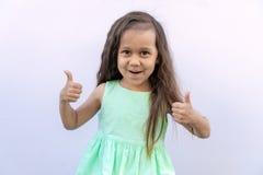 Kleines Mädchen mit dem braunen langen gelockten Haar lokalisiert auf weißem Hintergrund Kind, das zwei Daumen aufgibt stockbild