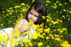 Kleines Mädchen mit dem dunklen Haar, das auf einem Feld von gelben Blumen auf dem Hintergrund sitzt Stockbild
