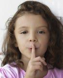 Kleines Mädchen mit dem Finger auf Lippen Stockfotos