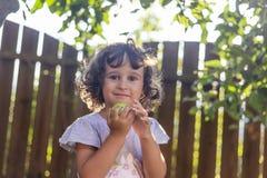 Kleines Mädchen mit dem gelockten Haar, das einen Apfel hält lizenzfreie stockbilder