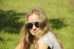 Kleines Mädchen mit dem Glasporträt sonnig auf Naturgras Lizenzfreie Stockfotografie