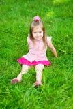 Kleines Mädchen mit dem langen blonden Haar, das auf Gras sitzt lizenzfreies stockfoto