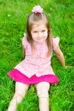 Kleines Mädchen mit dem langen blonden Haar, das auf Gras sitzt lizenzfreie stockbilder