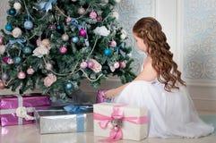 Kleines Mädchen mit dem langen Kraushaar, das nahe Weihnachtsbaum und Geschenken sitzt. Weihnachtszeit Lizenzfreie Stockfotos