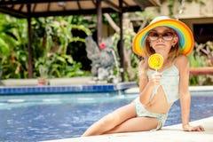 Kleines Mädchen mit dem Lutscher, der nahe dem Swimmingpool sitzt Stockbild