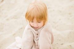 Kleines Mädchen mit dem roten Haar in einem Tuch am Strand Lizenzfreies Stockfoto