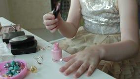Kleines Mädchen mit dem roten Haar malt Nägel mit rosa Lack, Blicke im Spiegel, Make-up, Gesicht, Mode, Art, Kosmetik stock video footage