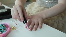 Kleines Mädchen mit dem roten Haar malt Nägel mit rosa Lack, Blicke im Spiegel, Make-up, Gesicht, Mode, Art, Kosmetik stock footage