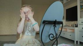 Kleines Mädchen mit dem roten Haar schmiert Creme, schaut im Spiegel, Make-up, Gesichtsbehandlung, Mode, Art, Kosmetik stock video