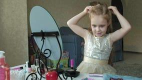 Kleines Mädchen mit dem roten Haar setzt eine Kante auf ihren Kopf, versucht auf Zusätzen, Blicke im Spiegel, Make-up, Gesicht, M stock footage