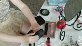 Kleines Mädchen mit dem roten Haar wählt Lidschatten, schaut im Spiegel, Make-up, Gesicht, Mode, Art, Kosmetik, Nahaufnahme stock video