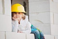 Kleines Mädchen mit dem Sturzhelm, der an Bau arbeitet Lizenzfreies Stockfoto