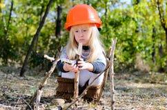 Kleines Mädchen mit dem Sturzhelm, der mit Stöcken spielt Lizenzfreie Stockbilder