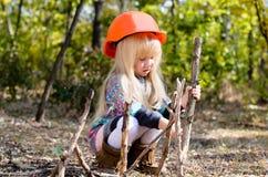 Kleines Mädchen mit dem Sturzhelm, der mit Stöcken spielt Stockfoto