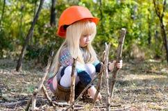Kleines Mädchen mit dem Sturzhelm, der mit Stöcken spielt Lizenzfreies Stockbild