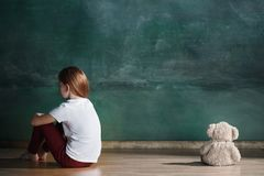 Kleines Mädchen mit dem Teddybären, der auf Boden im leeren Raum sitzt Autismus-Konzept Lizenzfreies Stockfoto