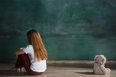 Kleines Mädchen mit dem Teddybären, der auf Boden im leeren Raum sitzt Autismus-Konzept Stockfotografie