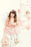 Kleines Mädchen mit dem weichen Spielzeug, das auf einem Stuhl sitzt Lizenzfreie Stockfotografie