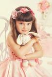 Kleines Mädchen mit dem weichen Spielzeug, das auf einem Stuhl sitzt Stockfoto