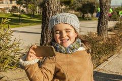 Kleines Mädchen mit der lustigen Kussgesichts- und -GRAUmütze, die ein selfie nimmt Lizenzfreies Stockbild