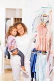 Kleines Mädchen mit der Mutter, die das ausgesuchte Kleid hält Stockfotos