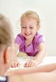 Kleines Mädchen mit der Mutter, die Domino spielt Lizenzfreie Stockbilder