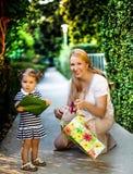 Kleines Mädchen mit der Mutter, die Geschenk hält Lizenzfreie Stockfotos