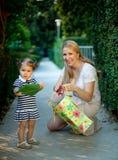 Kleines Mädchen mit der Mutter, die Geschenk hält Lizenzfreie Stockbilder