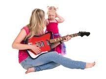 Kleines Mädchen mit der Mutter, die Gitarre spielt stockfotos