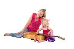 Kleines Mädchen mit der Mutter, die Gitarre spielt lizenzfreies stockfoto