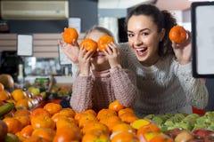 Kleines Mädchen mit der Mutter, die whith Mandarine in Abteilung frui aufwirft Lizenzfreie Stockbilder